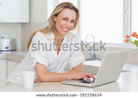 Happy woman using laptop at counter at home in the kitchen - stock photo