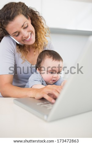 Happy woman using smartphone and laptop while sitting with baby boy at counter