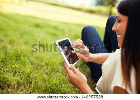 Happy woman using tablet outdoor laying on grass - stock photo