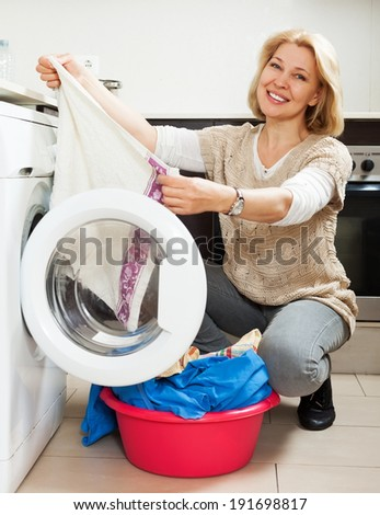 Happy woman using washing machine at home laundry