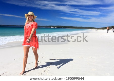 Happy woman walking along a beautiful white sandy beach in sunny Australia.  She is barefoot, wearing a sun hat, white shorts and a floaty top - stock photo
