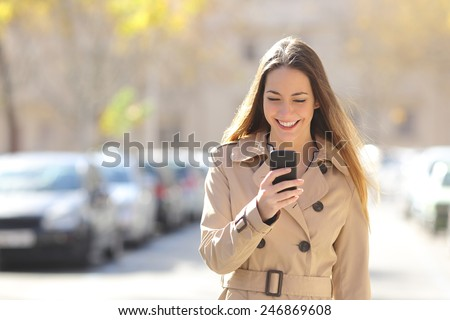 Happy woman walking and using a smart phone on the street in winter - stock photo