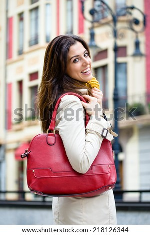 Happy woman walking down the street for shopping at european city wearing raincoat and handbag.  Autumn urban lifestyle and fashion concept. - stock photo
