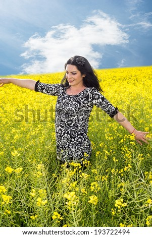Happy woman walking in rapeseed field and touching flowers - stock photo