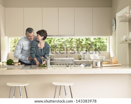 Happy woman washing vegetables while man hugging her from behind in kitchen - stock photo