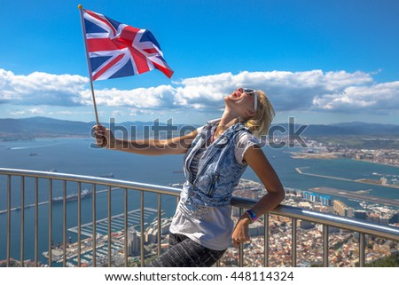 Happy woman waving a British flag on top of Gibraltar Rock. - stock photo