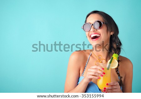 Happy woman wearing a bikini and sunglasses holding a cocktail, having fun isolated on bright blue background
