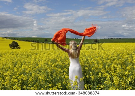 Happy woman wearing a long white dress and with scarf flailing in the air standing in a field of golden canola in rural Australia