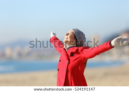 Happy woman wearing a red jacket breathing fresh air and raising arms on the beach in a sunny day of winter