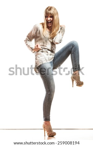 Happy woman wearing denim pants high heels. Girl in full length celebrating success clenching fist isolated - stock photo