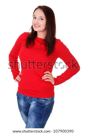 Happy woman wearing red blouse and jeans is standing and smiling with hands on hips. Isolated on white background.
