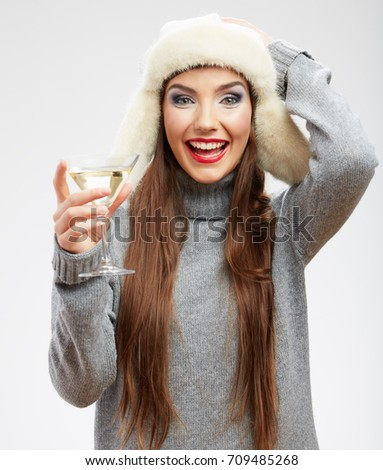 Happy woman wearing warm clothes drinking alcohol. Isolated portrait.