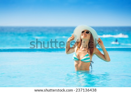 Happy woman wearing white hat in striped swimsuit stands in water of the ocean coast during holidays summer time - stock photo