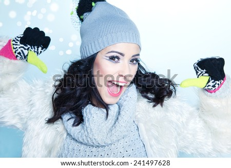 Happy woman wearing winter gloves covered with snowflakes.  - stock photo