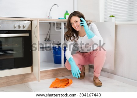 Happy Woman Wiping Leaking Water While Talking On Mobile Phone