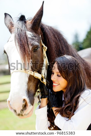 Happy woman with a beautiful horse smiling