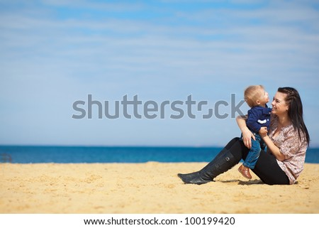 Happy woman with a child resting on the nature on the sea beach