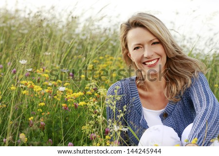 Happy woman with a flower relaxes in the grass with a flower - stock photo
