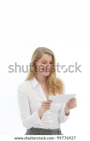 Happy woman with a gleeful grin reading good news in a letter which she is holding in her hands isolated on white
