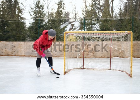 Happy woman with a hockey stick skating scores goal against - stock photo