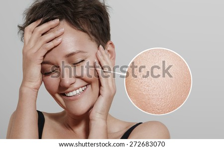 happy woman with a lens showing her ideal skin - stock photo