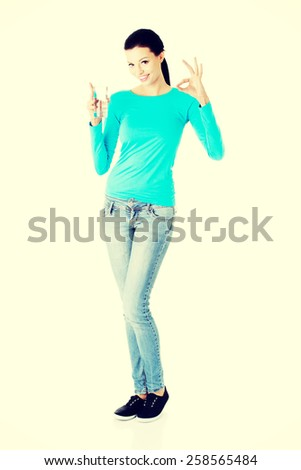 Happy woman with a water and showing perfect sign. - stock photo