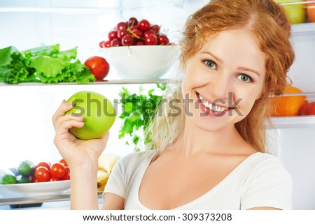 Happy woman with apple standing at the open refrigerator with fruits, vegetables and healthy food
