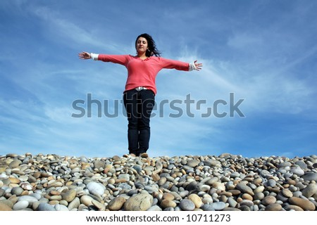 happy woman with arms wide open at the coast