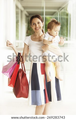 Happy woman with baby and shopping bags