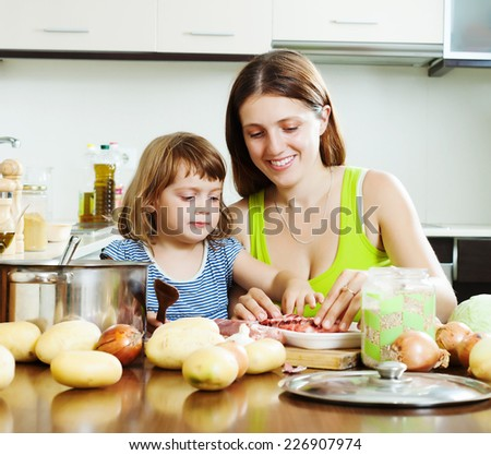 Happy woman with baby cooking with meat and vegetables together