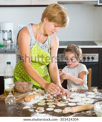 Happy woman with baby girl cooking meat ravioli (pelmeni) together