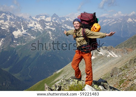 Happy woman with backpack standing on a mountain jad
