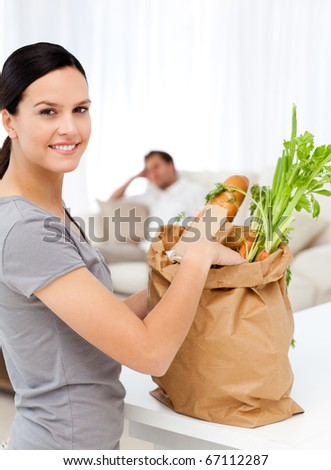 Happy woman with bags in the kitchen after shopping at the market - stock photo