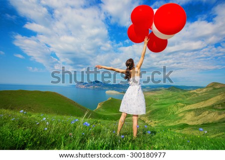 Happy woman with balloons into the field with green grass on the background of beautiful landscape. Celebration on nature outdoors.