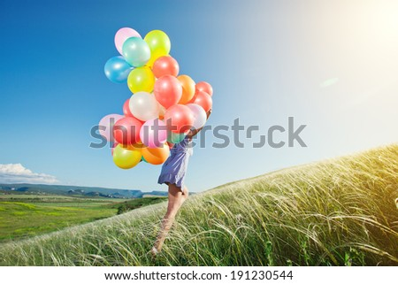 Happy woman with balloons running on the green field. - stock photo