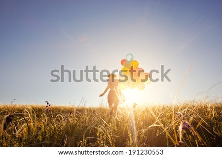 Happy woman with balloons running on the green field at sunset.