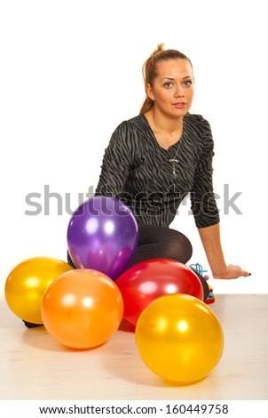 Happy woman with balloons sitting on floor  - stock photo