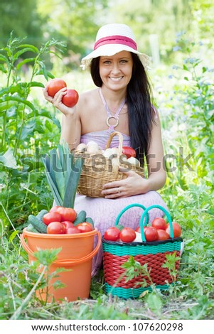 Happy  woman with basket of harvested vegetables in garden - stock photo