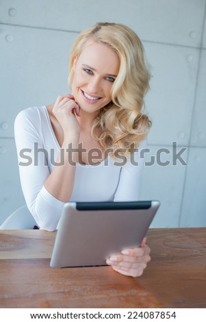 Happy woman with beautiful curly blond hair sitting at a table holding a tablet computer smiling at the camera