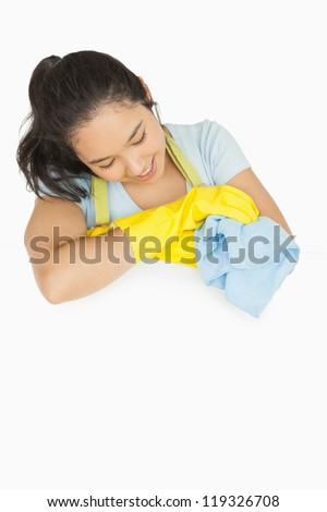 Happy woman with blue rag leaning on white surface wearing rubber gloves and apron - stock photo