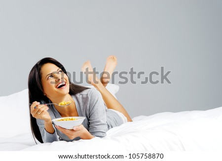 Happy woman with bowl of cornflakes eating breakfast in bed. healthy start to the day - stock photo