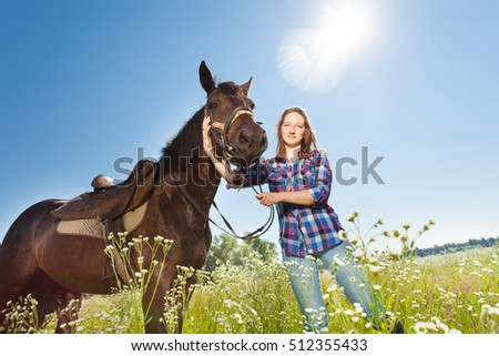 Happy woman with brown stallion in countryside