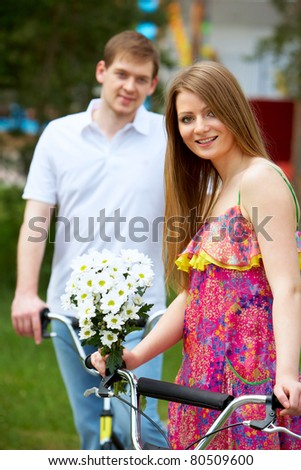 Happy woman with bunch of flowers looking at camera with her boyfriend on background