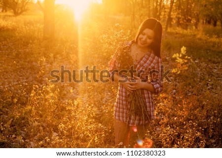 Happy Woman with bunch of wildflowers in her hands In front of Sunset