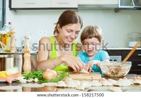 Happy woman with child cooking fish pelmeni (pelmeni), today together