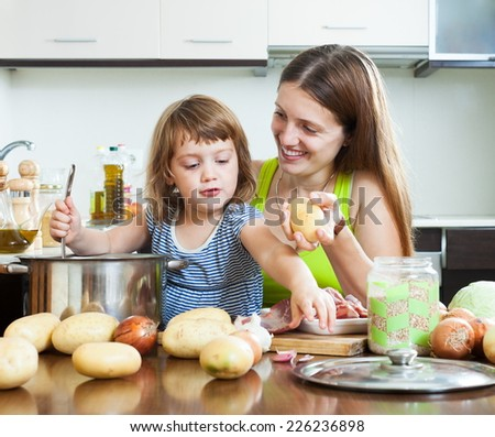Happy woman with child cooking with meat and vegetables - stock photo