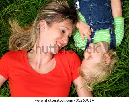 Happy woman with child on the green grass