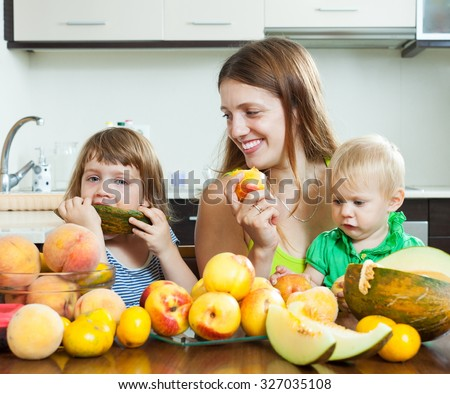 Happy woman with children eating melon and other fruits over  table at home interior