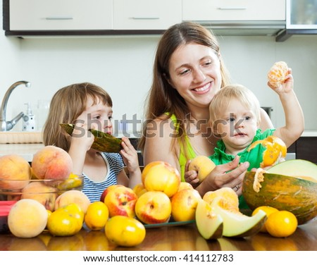 Happy woman with children eating melon and peaches over table at home interior