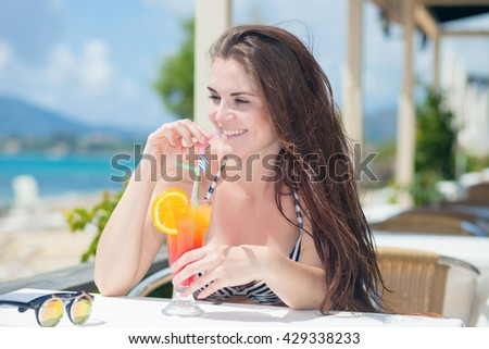 Happy woman with cocktail in the beach bar during tropical vacation